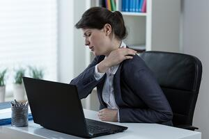 woman neck and shoulder pain in the office