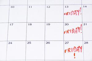 Close-up of white monthly calendar with FRIDAY! written in red