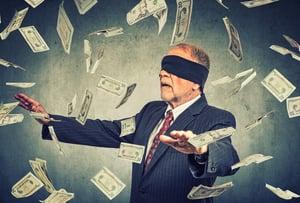 blindfolded-business-man-catching-money-1000x678